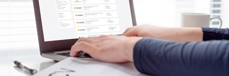 Bilde som viser deler av en åpen laptop. To hender hviler på tastaturet. Ved sidene av laptopen befinner det seg papir og penn på venstre side og en kaffekopp på høyre side.