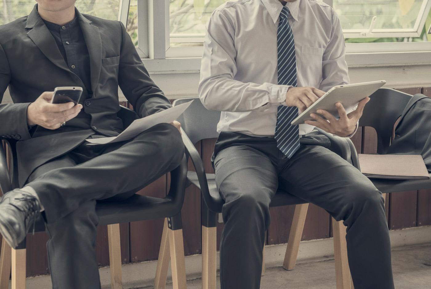 Bilde av to menn som sitter ved siden av hverandre. Det er ikke mulig å se ansiktene deres. De er ikledd dress og det virker som om de venter på å bli kalt inn til intervju. Den ene mannen holder en mobil og et papir i hånden. Den andre mannen har tatt av seg dressjakka og holder en pad i hånden.