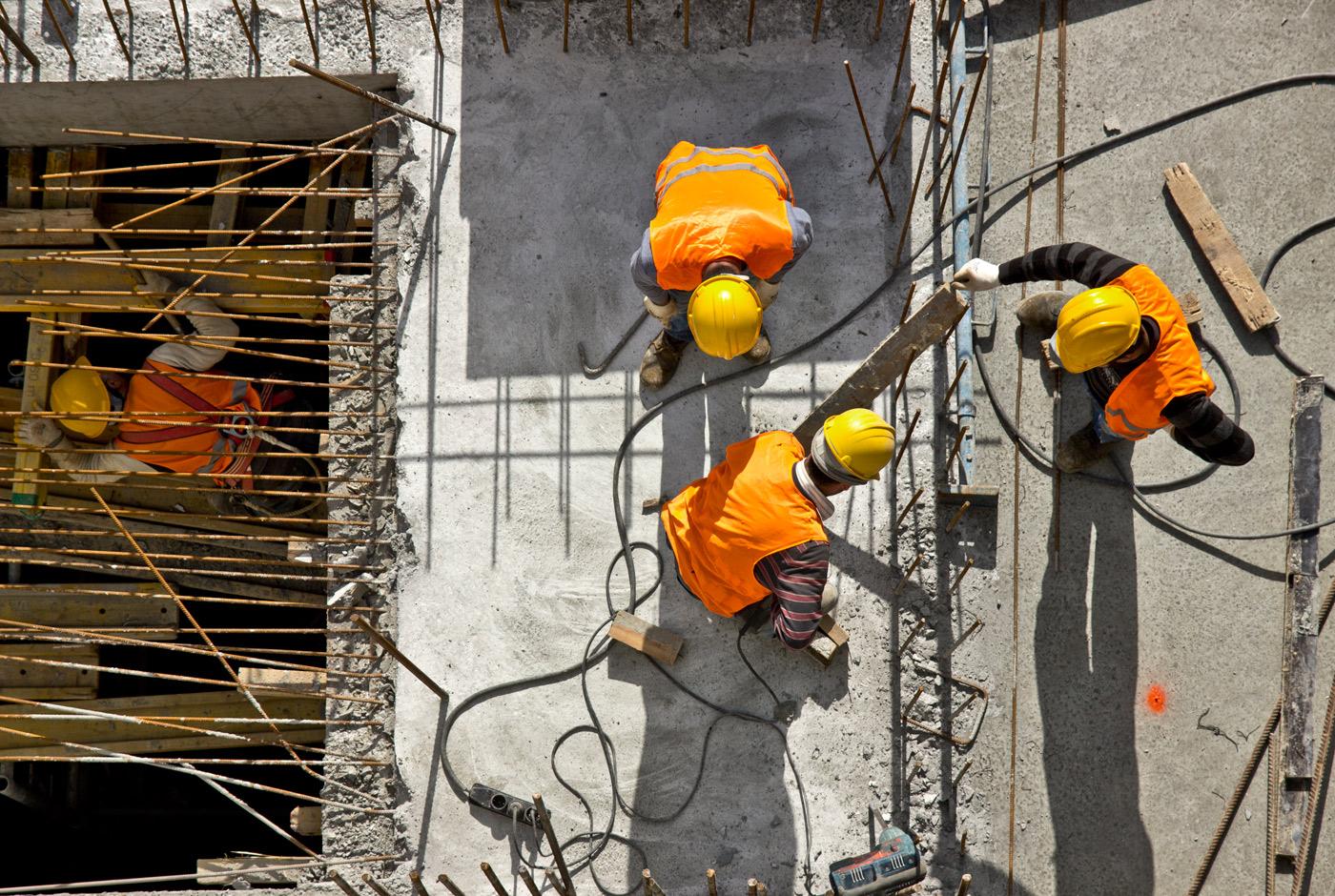 Bilde i fugleperspektiv som viser fire anleggsarbeidere på en byggeplass. De har på seg gule hjelmer og oransje vester.