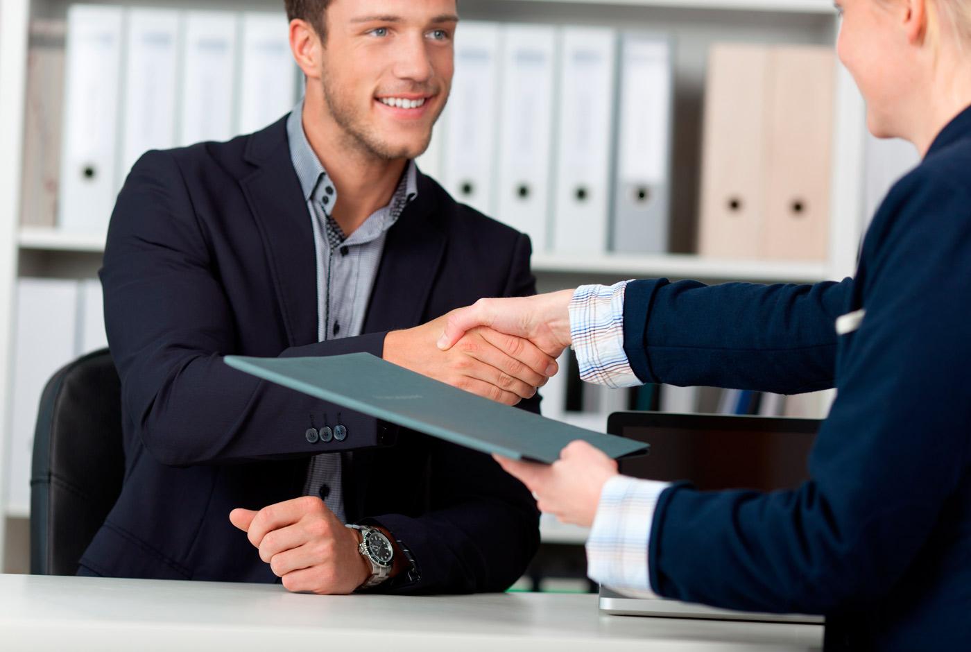 Bilde fra en rekrutteringsprosess. En mann sitter ved et skrivebord og smiler mens han håndhilser på en kvinne. De er begge ikledd dress og kvinnen holder en mappe I hånden. I bakgrunnen kan en rekke permer skimtes.
