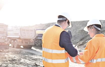 Bilde fra en utendørs arbeidsplass. To arbeidere med hvit hjelm og oransje vester står med ryggen til. I bakgrunnen skimtes tre lastebiler for transport av stein.