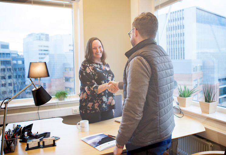 Bilde fra et kontor. En kvinnelig arbeidsgiver håndhilser på en mannlig kandidat. De står på hver sin side av en kontorpult.